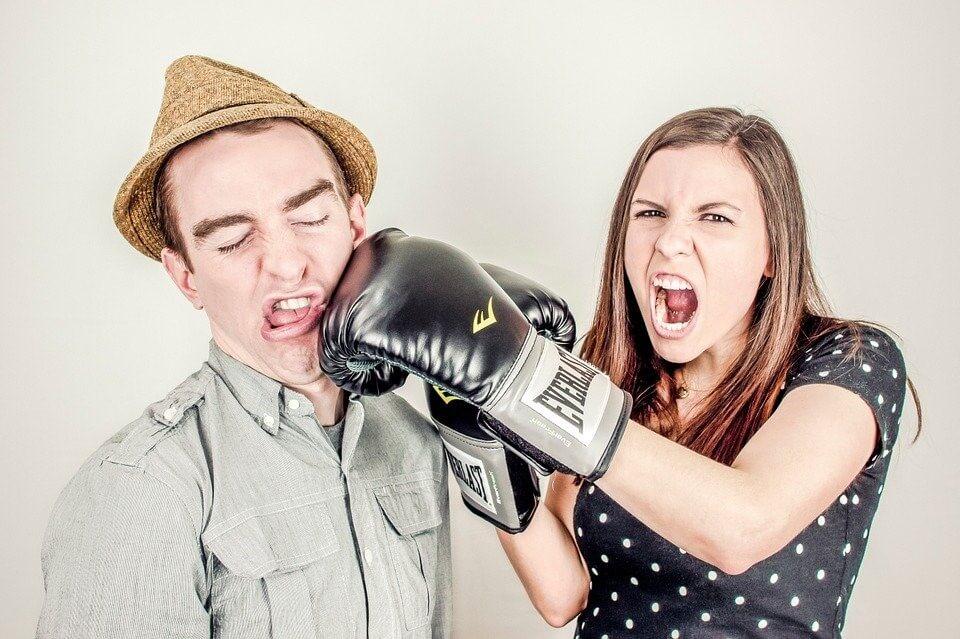 fille qui donne un coup de poing à son petit ami avec des gants de boxe