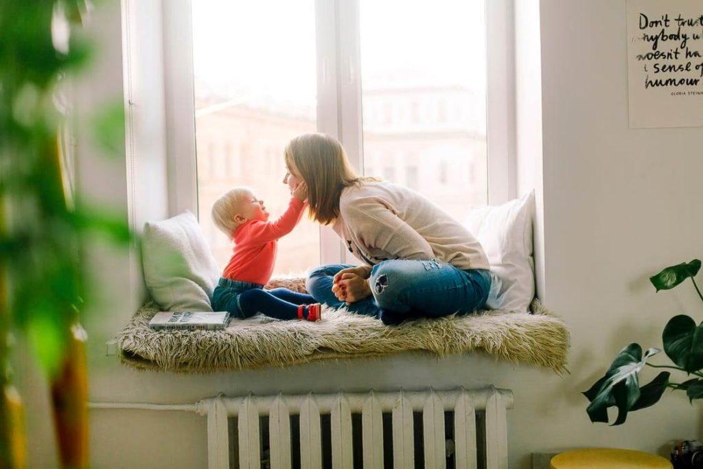 mère qui joue avec son bébé devant une fenêtre