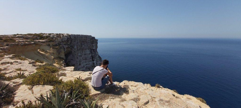 jeune fille assise au bord des falaises de Dingli Cliffs à Malte