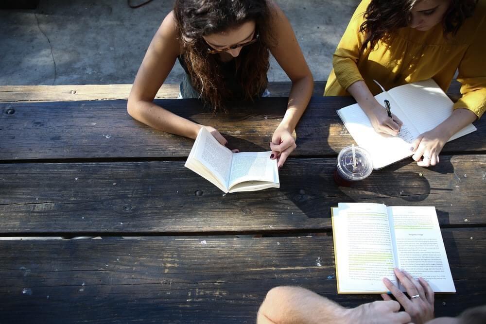 groupe de jeunes filles qui lisent à l'extérieur
