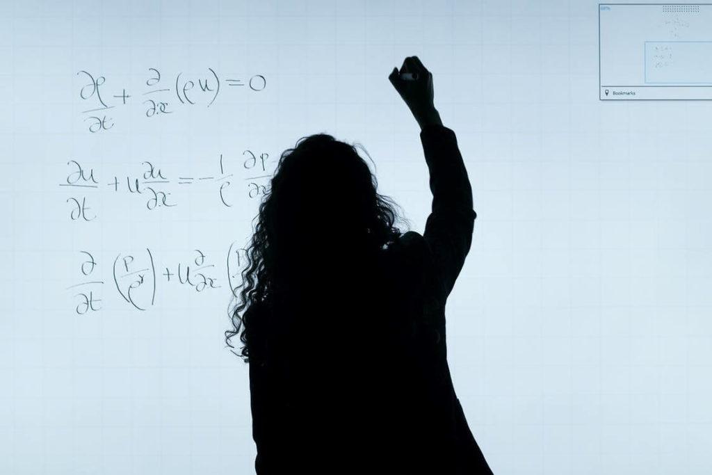 femme écrivant des formules de maths sur un tableau blanc