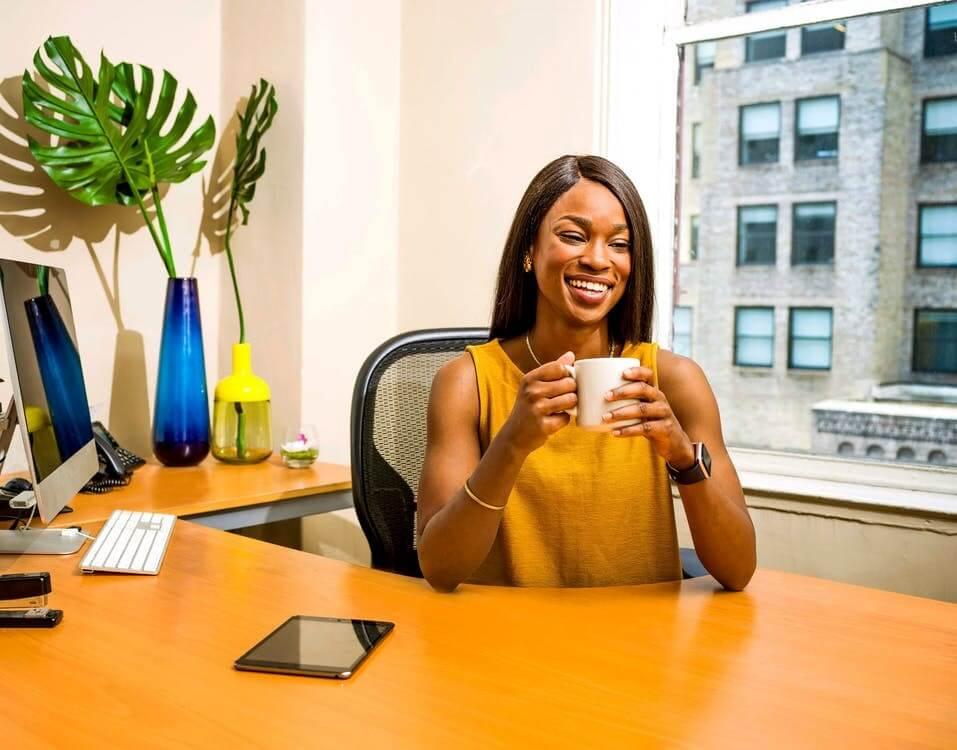jeune femme buvant un café à son bureau
