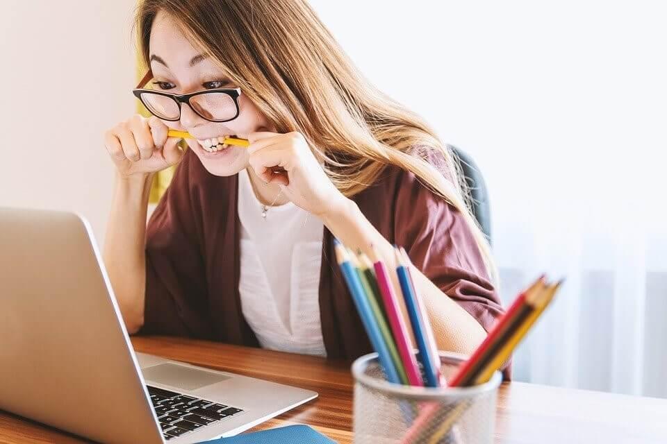 jeune femme qui travaille sur un ordinateur avec un crayon entre les dents