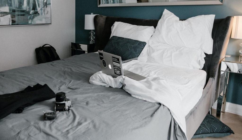 ordinateur et appareil photo posés sur un lit