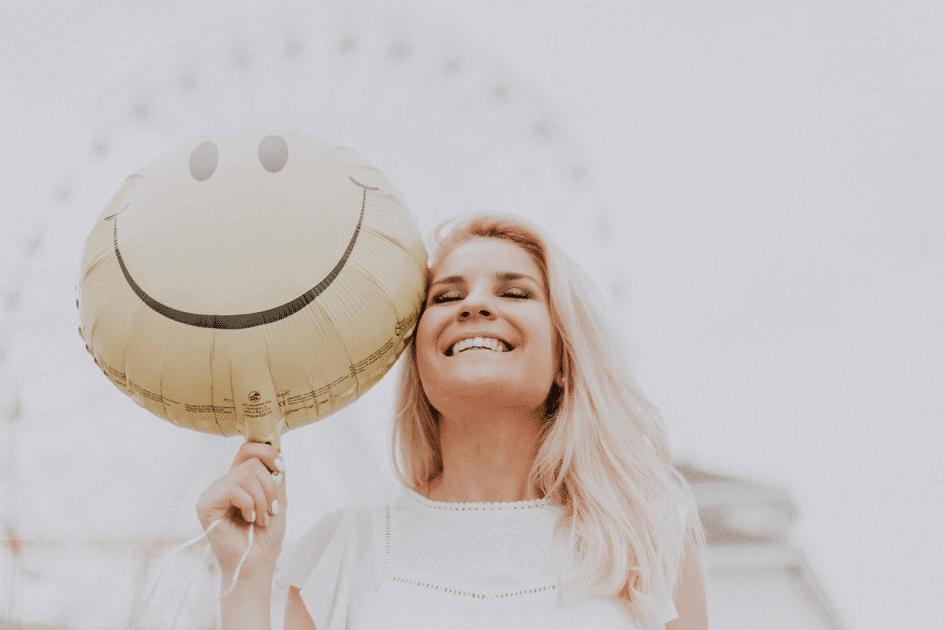 femme blonde avec un ballon qui sourit