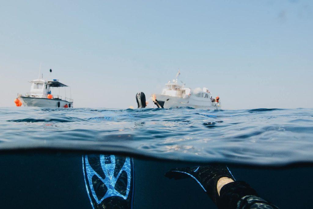 plongeur sous l'eau à côté des bateaux