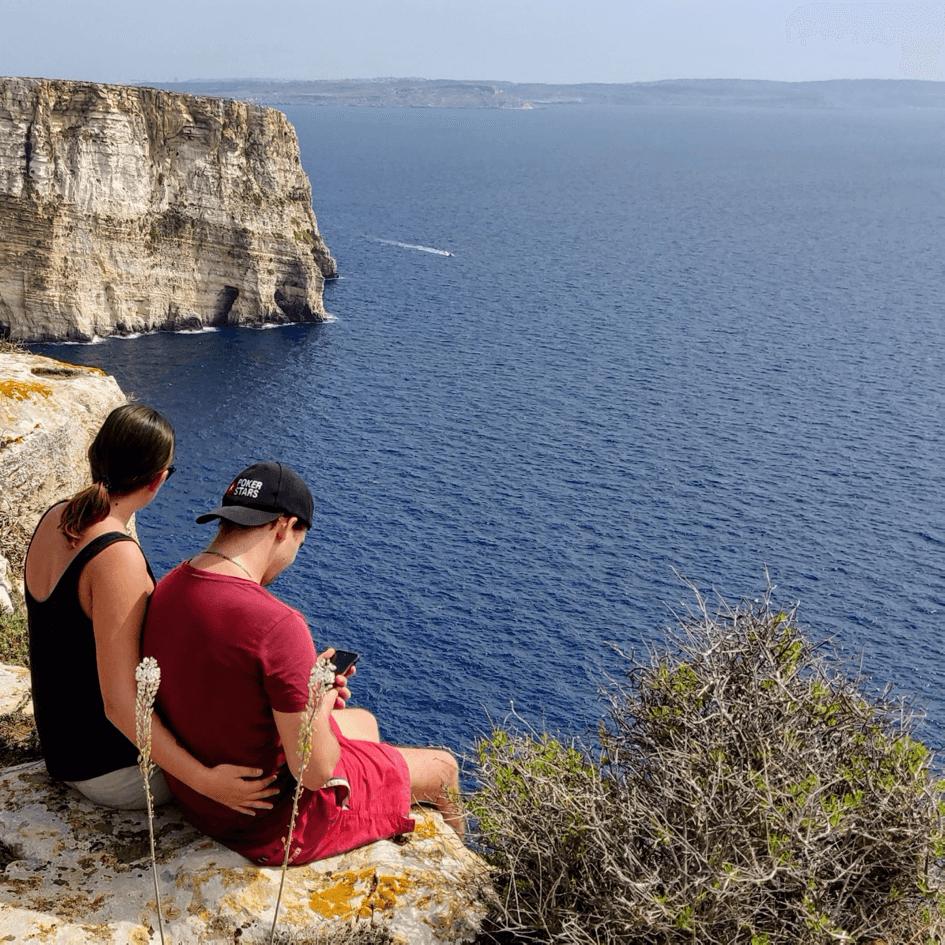 Soline et son copain face à la mer en haut d'une falaise à Malte